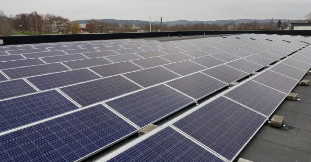 Bilden visar solpaneler på tak, byggda av Paneltaket.