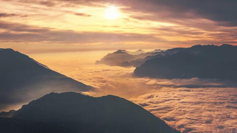 bilden visar sol över moln och berg